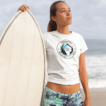 tee-mockup-of-a-blonde-woman-standing-at-the-beach-next-to-her-surfboard-26820